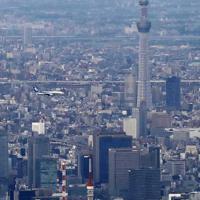 羽田空港の新飛行ルートの実機飛行確認が始まり、都心上空を飛行する航空機=東京都大田区で2020年2月2日午後5時8分、本社ヘリから
