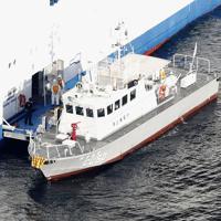 横浜・大黒ふ頭沖に停泊するクルーズ船「ダイヤモンド・プリンセス」に横付けされた海上保安庁の巡視艇=2020年2月5日午前8時26分、本社ヘリから