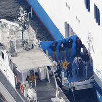 横浜・大黒ふ頭沖に停泊するクルーズ船「ダイヤモンド・プリンセス」から、横付けされた海上保安庁の巡視艇に移動する関係者とみられる人たち=2020年2月5日午前8時54分、本社ヘリから