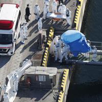 クルーズ船「ダイヤモンド・プリンセス」内で陽性反応を示した乗船者を搬送する防護服姿の関係者=横浜市中区で2020年2月5日午前9時23分、本社ヘリから