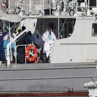 クルーズ船「ダイヤモンド・プリンセス」内で新型コロナウイルスへの感染が確認され、白い布をかぶった状態で巡視艇で待機する乗客たち=横浜市中区で2020年2月5日午前10時10分、喜屋武真之介撮影(画像の一部を加工しています)