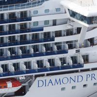 物資補給などのため、横浜港の大黒ふ頭に着岸するクルーズ船「ダイヤモンド・プリンセス」。マスク姿の乗客も見える=2020年2月6日6日午前9時9分、本社ヘリから