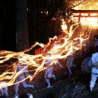たいまつを手に、神社からの急な石段を駆け下りる白装束の男たち=和歌山県新宮市で2020年2月6日午後7時50分、小出洋平撮影
