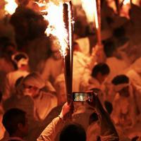 たいまつを手に写真を撮る白装束の男=和歌山県新宮市で2020年2月6日午後7時39分、小出洋平撮影