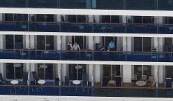 横浜港の大黒ふ頭沖に停泊するクルーズ客船「ダイヤモンド・プリンセス」。手を振る乗客の姿が見える。乗客乗員は計3700人以上で、新型コロナウイルスへの感染が確認された人もいた=2020年2月4日午後4時3分、本社ヘリから