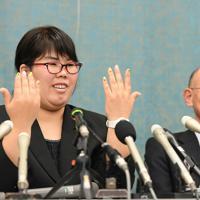滋賀県東近江市の湖東記念病院で2003年、入院中の男性患者(当時72歳)の人工呼吸器を外して殺害したとして、殺人罪で懲役12年が確定し、服役した西山美香さん。再審(やり直しの裁判)の初公判で検察側は新たな有罪立証をしないと表明し、西山さんの無罪が確実となった。記者会見でヒマワリが描かれた爪を示して笑顔を見せる西山さん(左)と井戸謙一弁護団長=大津市で2020年2月3日、山田尚弘撮影