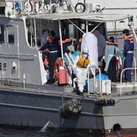 クルーズ船「ダイヤモンド・プリンセス」内で新型コロナウイルスへの感染が確認され、白い布をかぶった状態で巡視艇で搬送される一部の乗船者たち=横浜市中区で2020年2月5日、喜屋武真之介撮影