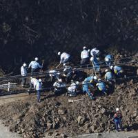 道路脇の斜面が崩れ、通行していた18歳の女子高生が巻き込まれて死亡した現場を調べる消防、警察関係者ら=神奈川県逗子市で2020年2月5日、本社ヘリから