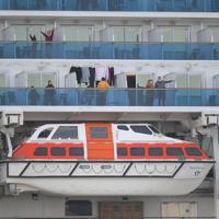 新たに乗客41人の新型コロナウイルス感染が判明したクルーズ船「ダイヤモンド・プリンセス」で、下船が許されずベランダに出て運動したり、他の部屋の人と話したりして過ごす乗船客ら=横浜市鶴見区の大黒ふ頭で2020年2月7日、手塚耕一郎撮影