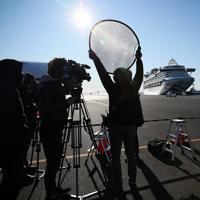 着岸したクルーズ船「ダイヤモンド・プリンセス」(奥)と集まった報道陣=横浜市鶴見区の大黒ふ頭で2020年2月9日午前8時32分、吉田航太撮影