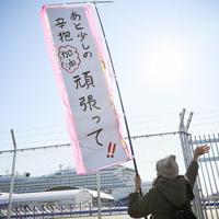 着岸したクルーズ船「ダイヤモンド・プリンセス」に向け、励ましのメッセージを掲げながら手を振る女性=横浜市鶴見区の大黒ふ頭で2020年2月9日午後2時3分、吉田航太撮影