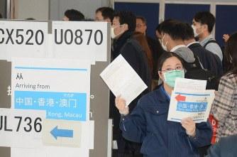 プラカードと質問票を持ち、到着客を誘導する検疫所の職員=成田空港で2020年2月7日、中村宰和撮影