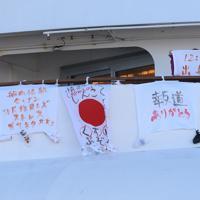 停泊するクルーズ船「ダイヤモンド・プリンセス」からメッセージを送る女性=横浜市鶴見区の大黒ふ頭で2020年2月11日午前9時33分、丸山博撮影