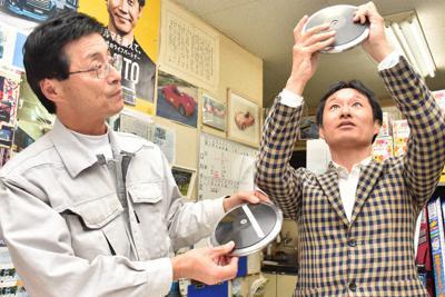 手掛けた円盤を手にする斉藤秀雄社長(左)と瀬尾和哉教授=山形県中山町の斉藤クラフトで