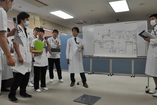 新型コロナウイルス感染者の来院を想定した机上訓練。医師らは「パニックにならないように」と呼びかけた=山梨大医学部付属病院で2020年1月31日