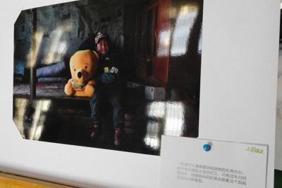 北京であった留守児童支援イベントで展示されていた写真。離れて暮らす母親から送られたぬいぐるみを少年が抱いていた=2020年1月10日、津啓介撮影