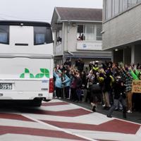 中国・武漢市から帰国し千葉県勝浦市のホテルに身を寄せていた人を乗せたバスを見送る地元住民たち=千葉県勝浦市で2020年2月13日午前9時34分、滝川大貴撮影