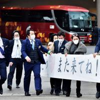 バスで帰宅する中国・武漢市から帰国し千葉県勝浦市のホテルに身を寄せていた人たちを見送ろうと「また来てね!」などと書かれた横断幕を用意する地元住民ら=千葉県勝浦市で2020年2月13日午前8時48分、滝川大貴撮影