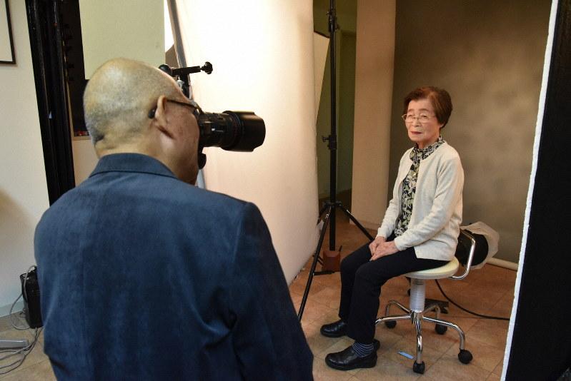 お客さんの白子とよさんを撮る能津喜代房さん=東京都中野区で、筆者撮影