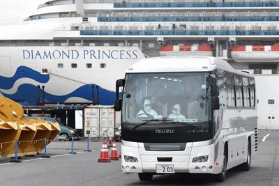運転手らが防護服を着用し、一部の乗客が下船したクルーズ船「ダイヤモンド・プリンセス」(奥)から出発するバス=横浜市鶴見区で2020年2月14日午後2時52分、竹内紀臣撮影