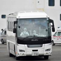 運転手らが防護服を着用し、一部の乗客が下船したクルーズ船「ダイヤモンド・プリンセス」(奥)から出発するバス=横浜市鶴見区で2020年2月14日午後2時43分、竹内紀臣撮影
