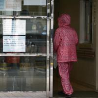 新型コロナウイルスへの感染対策にかっぱを着用し、入院患者を見舞うため済生会有田病院へ入る女性=和歌山県湯浅町で2020年2月14日午前9時6分、小出洋平撮影
