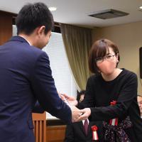田丸雅智・審査員長(左)からトロフィーを受け取る高野ユタさん。本人の希望でマスクを着用して出席した=松山市役所で2020年2月14日、中川祐一撮影