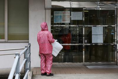新型コロナウイルスへの感染対策にかっぱを着用し、入院患者を見舞うため済生会有田病院を訪れた女性=和歌山県湯浅町で2020年2月14日午前9時6分、小出洋平撮影