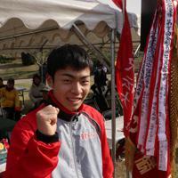 総合優勝が決まり、優勝旗の前で喜ぶ土屋選手=御所市で、稲生陽撮影