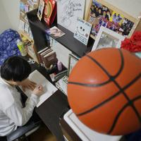 帰宅後、部屋で「バスケノート」を書く浜田静里奈さん。机には女子バスケット元日本代表の大神雄子さんのサインなどが並ぶ。震災の年の5月、家やバスケット道具を流された女川の子供たちのために、支援に訪れてくれた=仙台市青葉区で2019年12月、和田大典撮影