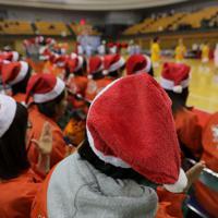クリスマスをはさんで開かれるウインターカップの初戦を戦う明成の選手たちを、サンタクロースの帽子をかぶって応援する保護者たち=東京都八王子市で2019年12月、和田大典撮影