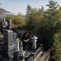 東日本大震災で亡くなった家族の墓で、線香を手向ける浜田亮子さん=宮城県女川町で2019年12月、和田大典撮影