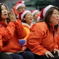 ウインターカップ初戦、シュートしたボールを見つめる浜田亮子さん(右)ら明成の保護者たち=東京都八王子市で2019年12月、和田大典撮影