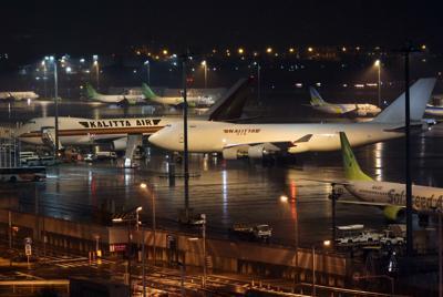 クルーズ船「ダイヤモンド・プリンセス」の米国人乗客乗員を帰国させるため、羽田空港に到着した2機の米国チャーター機(中央と左)=2020年2月16日午後10時39分、小川昌宏撮影
