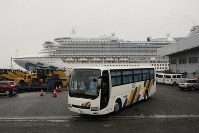 A bus leaves the quarantined Diamond Princess cruise ship at a port, on Feb. 16, 2020, in Yokohama, near Tokyo. (AP Photo/Jae C. Hong)