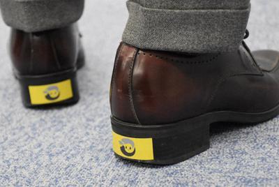 靴のかかとに貼った小諸市のステッカー。暗い所では光を反射する=長野市で