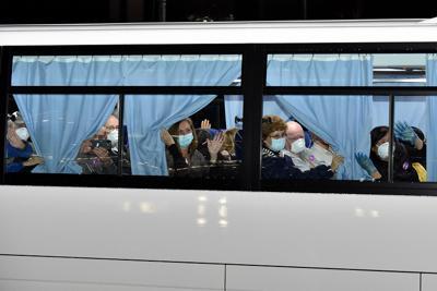 クルーズ船「ダイヤモンド・プリンセス」から下船し、羽田空港に向かうバスの中からカーテンを開いて報道陣に手を振る米国人乗客ら=横浜市鶴見区の大黒ふ頭で2020年2月17日午前1時37分、竹内紀臣撮影