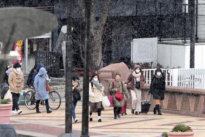 雪の降る中を寒そうに歩く人たち=福岡市博多区で2020年2月17日午前10時23分、須賀川理撮影