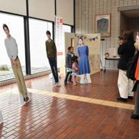 「スカーレット」のトークショー会場に飾られたパネルを撮影する来場者ら=滋賀県甲賀市水口町水口のあいこうか市民ホールで2019年12月14日午後0時49分、成松秋穂撮影