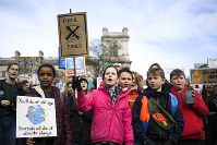 Children gather at Parliament Square holding placards and flags, as they protest against climate change, in London, Feb. 14, 2020.(AP Photo/Alberto Pezzali)