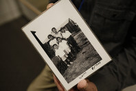 In this photo taken Feb. 11, 2020, Les Ouchida holds a 1943 photo of himself, front row, center, and his siblings taken at the internment camp his family was moved to, as he poses at the permanent exhibit titled