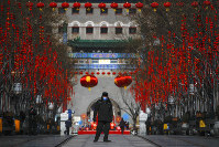 A security guard wearing a face mask walks through a quiet main Qianmen Street, a popular tourist spot, in Beijing, on Feb. 16, 2020. (AP Photo/Andy Wong)