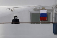 A quarantined passenger on the Diamond Princess cruise ship stands on the balcony of his cabin next to a Russian flag, on Feb. 15, 2020, in Yokohama, near Tokyo. (AP Photo/Jae C. Hong)