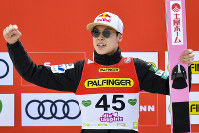 Ryoyu Kobayashi from Japan celebrates on the podium after he placed second in the ski flying competition during the Ski Jumping World Cup in Bad Mitterndorf, Austria, on Feb. 16, 2020. (AP Photo/Kerstin Joensson)