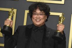 アカデミー賞受賞者に贈られるオスカー像を手に笑顔を見せるポン・ジュノ監督=米西部カリフォルニア州ハリウッドで2020年2月9日、AP
