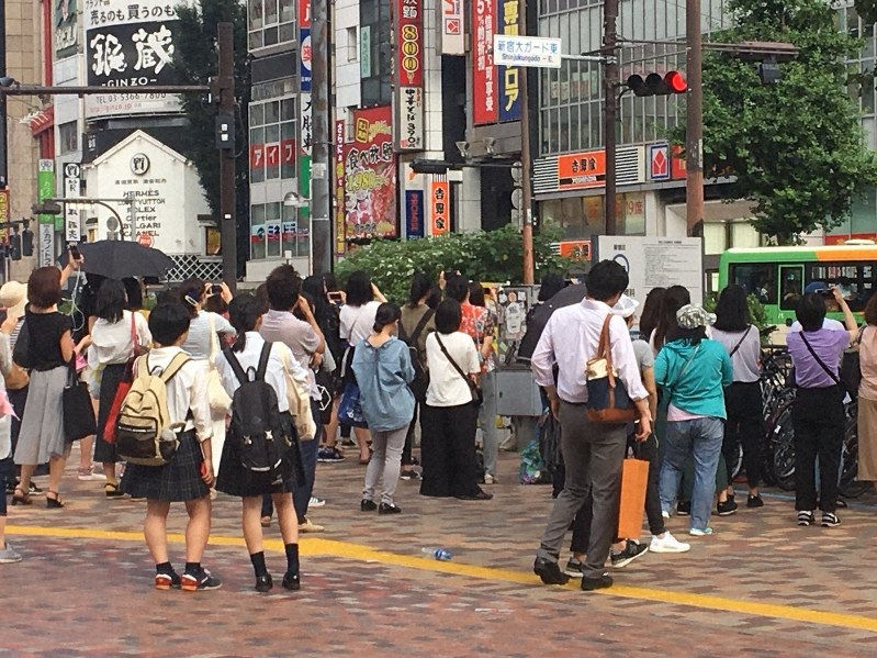 男性アイドルグループのライブ映像を見つめる若者たち=東京・新宿の西武新宿駅前で2018年7月8日撮影