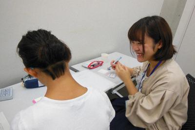 「彩の国子ども・若者支援ネットワーク」が運営する学習支援教室で、生徒に話しかけるボランティアの大学生(右)=埼玉県内で