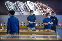In a Feb. 14, 2020 file photo, employees wear face masks as they stand in a reopened Apple Store in Beijing. (AP Photo/Mark Schiefelbein)