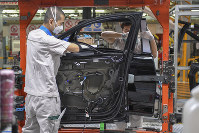 In this Feb. 17, 2020, photo and released by Xinhua News Agency, workers assemble Audi A6 L cars at a workshop of FAW-Volkswagen Automobile Co., Ltd. in Changchun, northeast China's Jilin Province. (Zhang Nan/Xinhua via AP)