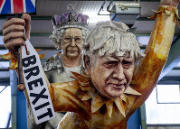 Figures depicting British Prime Minister Boris Johnson, right, and the Queen Elizabeth II are shown during a press preview for the Mainz carnival, in Mainz, Germany, on Feb. 18, 2020. (AP Photo/Michael Probst)